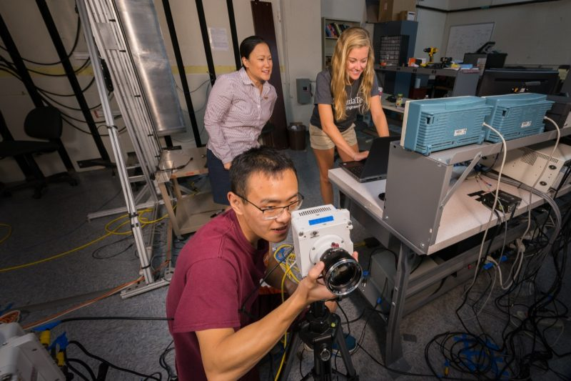 Dr. Ikeda-Gilbert instructs undergraduate AOE student, Rebecca Keller, and graduate AOE student, Zhongshu Ren on how to properly focus one of two high-speed Phantom VEO 710S cameras in preparation for a flexible wedge drop test.