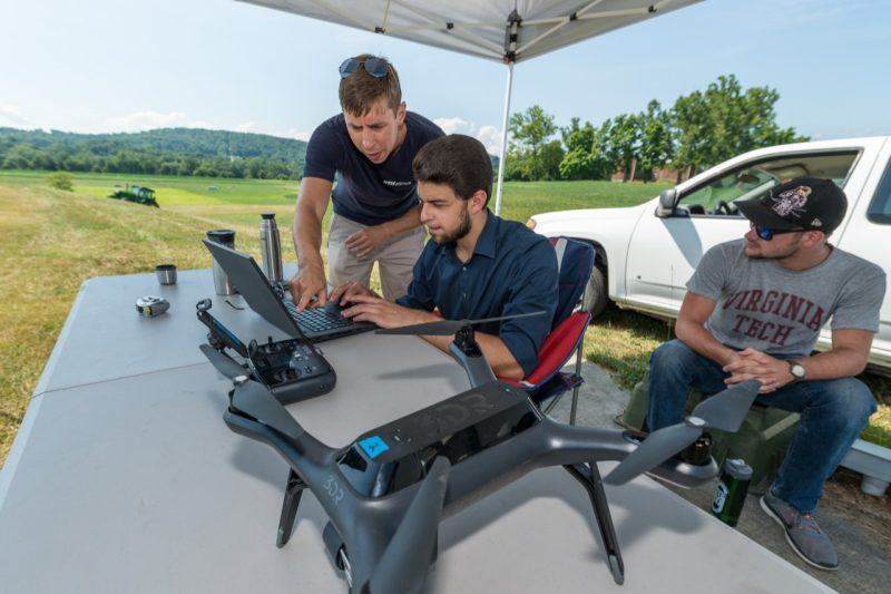 Hunter McClelland, Arun Das, and Charles Watson prepare two quadrotors for an infrastructure inspection task