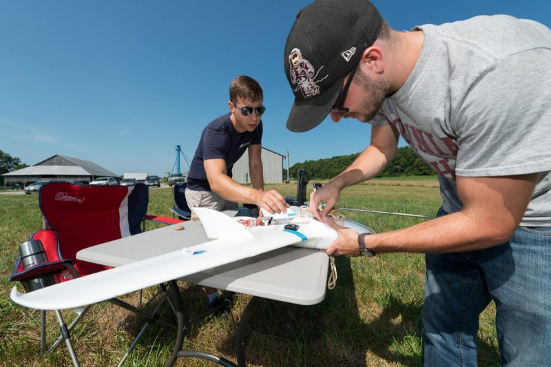 Hunter McClelland and Charles Watson prepare a small fixed-wing UAS for a wind-sensing mission.