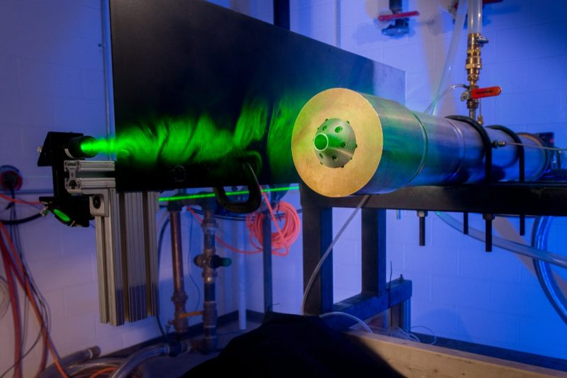 A laser illuminates the flowfield of a free jet for Doppler-based speed measurements.