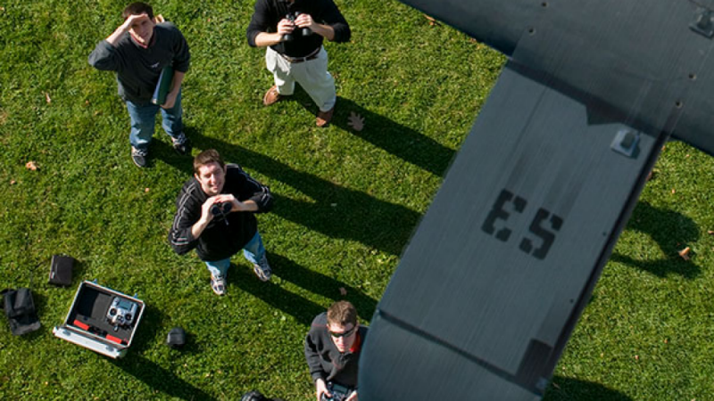 Students look up at a drone